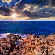 Sea ??wave breaks about boulders at sunset Stock Photos