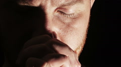 Young man praying in dark atmosphere: God, religion, meditation, deep, intense Stock Footage