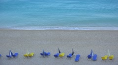 Blue and yellow sea lounge sunbeds on beach, turquoise water waving Stock Footage