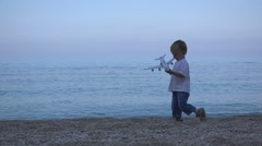 Little child with airplane toy playing on a beach, turquoise water  Stock Footage