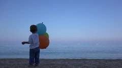 Little child on beach playing with colored balloon admiring the turquoise sea  Stock Footage