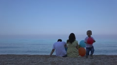 Little boy walking parents sitting on the beach, turquoise sea, blue sky  Stock Footage