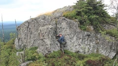 Hiker climbing up on the rocky wall in the mountain Stock Footage