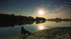 NO BIRDS: The man sitting by picturesque lake evaporation - early morning time Stock Footage