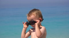 Funny boy try to arrange sunglasses, annoyed to fail, beautiful turquoise sea 4K - stock footage
