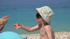 Stock Video Footage of Little child refuse sun lotion, mother try to apply sun cream, blue sea