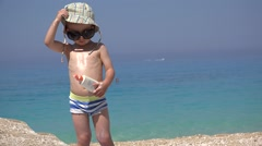 Amusing child applying sun lotion to himself, sunglasses, turquois sea waving Stock Footage