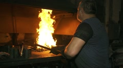 Factory worker stirring a fire in an oven in slow motion - stock footage