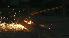 Factory worker cutting iron, small glowing sparks fall in slow motion Stock Footage