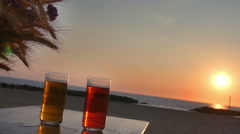 Two glasses of non alcoholic cocktails on a table near the sea: sunset, summer Stock Footage