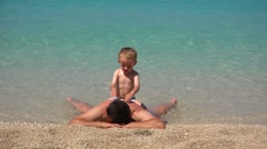 Father laying on the seashore, baby playing, turquoise sea  Stock Footage