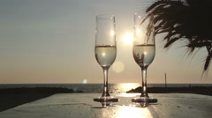 Pouring glasses with sparkling white wine by the beach: summer, sunset, sea Stock Footage
