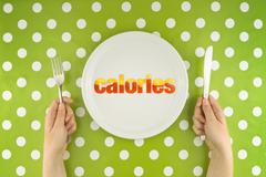 hands at the table with calories on plate - stock photo