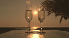 Two glasses of wine at the sunset by the sea: love, aperitif, drinking, fun Stock Footage