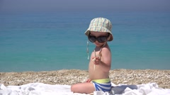 Little boy with big sunglasses play with sea star, turquoise sea waving 4K - stock footage