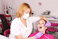Female dentist and girl patient dental exam Stock Photos