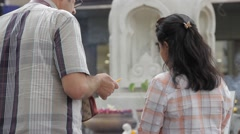 Westerner helping buddhist friend / girlfriend / wife with prayer Stock Footage