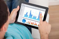 Cropped image of man analyzing graphs on digital tablet at home Stock Photos
