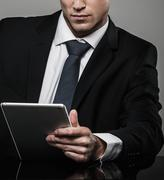 well-dressed man in black suit with tablet pc - stock photo