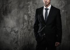 well-dressed man in black suit against grunge wall - stock photo
