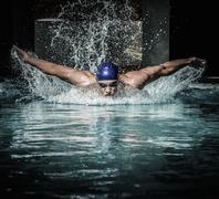 young man in swimming cap and goggles swim using breaststroke technique - stock photo
