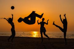 silhouettes a young people having fun on a beach against sunset - stock photo