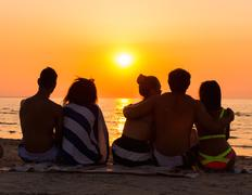 silhouettes a young people sitting on a beach looking at  sunset - stock photo