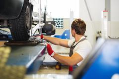 Young serviceman checking wheel alignment  in a car workshop Stock Photos