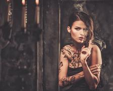 Smoking tattooed beautiful woman  in old spooky interior Stock Photos