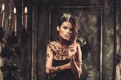 smoking tattooed beautiful woman  in old spooky interior - stock photo