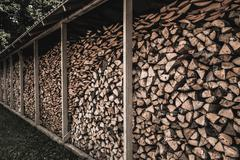 stockpile of sawed logs under shed - stock photo
