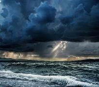 Heavy rain over stormy ocean Stock Photos