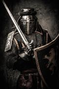 medieval knight with a sword against stone wall - stock photo