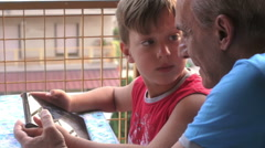 Young boy playing with tablet pc: games, entertainment, fun, child, grandfather  Stock Footage