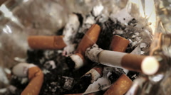 Cigarette still burns into ashtray: depression, loneliness, cancer,  Stock Footage