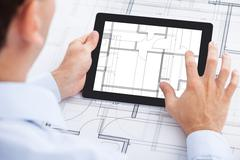 Cropped image of architect analyzing blueprint on digital tablet in office Stock Photos