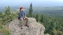 Hiker sits on a rock in the mountains and admires views Stock Footage