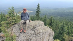 Hiker sits on a rocky cliff in the mountains. Stock Footage