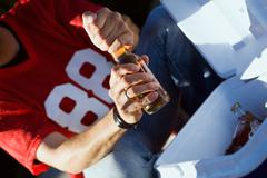 tailgating: anonymous man opening bottle of beer - stock photo