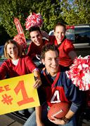 tailgating: excited fans cheering for team and holding sign - stock photo