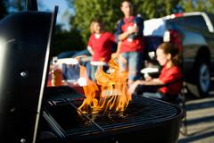 tailgating: flames rise as charcoal is prepped for cooking - stock photo