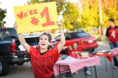 tailgating: woman holds up number one sign for team - stock photo