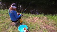 Woman sit on stump near pond, watch playing cat with small fish Stock Footage