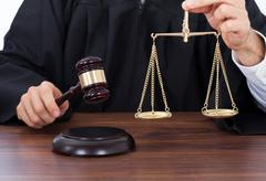 Midsection of male judge holding weight scale while striking gavel on block a Stock Photos