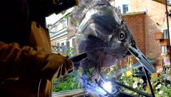 Welder making a metal fish sculpture Stock Footage