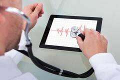 Doctor analysing the health of tablet computer Stock Photos