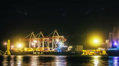 Unloading container cargo freight ship in container terminal in night time - stock footage