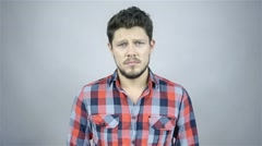 Handsome young man isolated over grey background. Funny face. Stock Footage