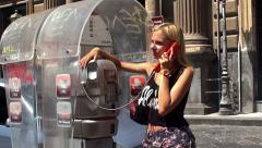 Girl talking on the phone in a street phone booth. Stock Footage