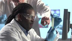 Male Scientists Examining Yellow Fluid in Vial - Close Stock Footage